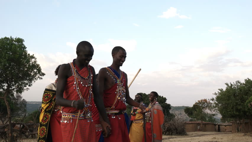 low angle shot of a group of maasai women and men from a village near maasai mara dancing in pairs