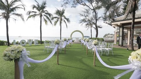 wedding set up in garden, park. outside wedding ceremony, celebration. wedding aisle decor. Rows of white wooden empty chairs on lawn before wedding ceremony.