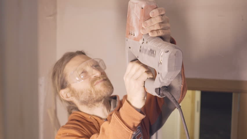 Handyman wearing protection glasses using noisy puncher machine to make a hole in the ceiling