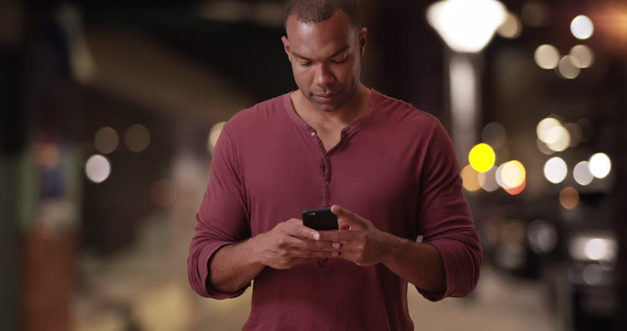 A black man texts on his mobile phone on a city street. An African American guy uses his smart phone in a metropolitan area. 4k | Shutterstock HD Video #22206409