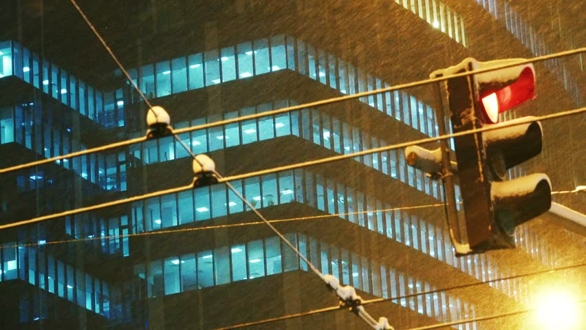 Snow is on the background of a modern office building in the business district of the city on a winter evening. The traffic light changes from red to green light.