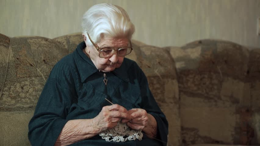 93-year-old woman sits at couch and knits lace napkin.