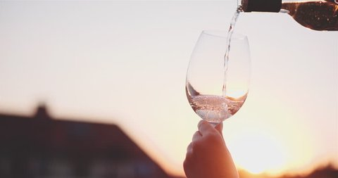 Cinemagraph - Pouring a Glass of White Wine agains the Sunset Sky. 120 fps, 4K DCi. Relaxing Cozy Evening on Terrace. Unrecogizable female hand holding a wineglass on patio. Motion photo. Lens Flare.