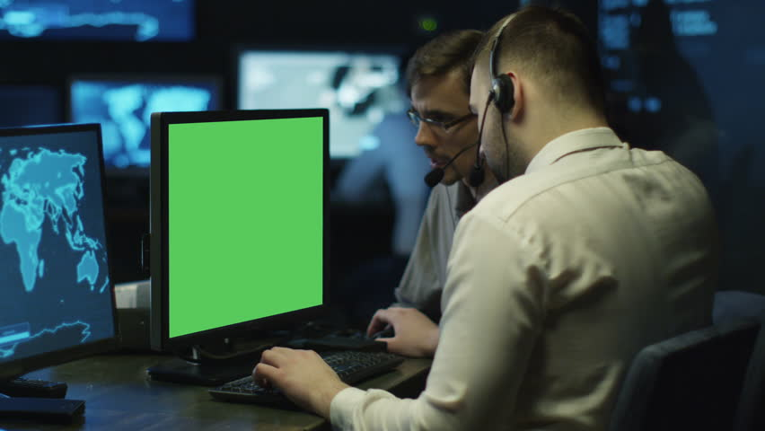 Concentrated Programmers Work on Personal Computers Located in a System Control Room. Computer has Green Screen.  Shot on RED Cinema Camera in 4K (UHD). | Shutterstock HD Video #22232479