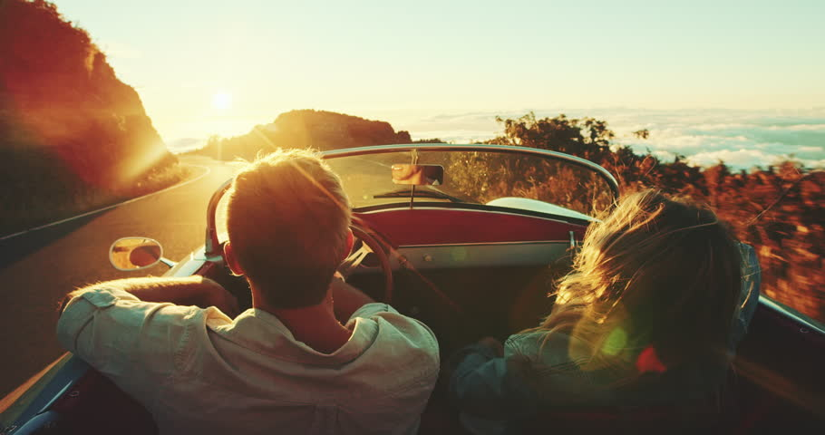 Happy couple driving on country road into the sunset in classic vintage sports car   Shutterstock HD Video #22242868