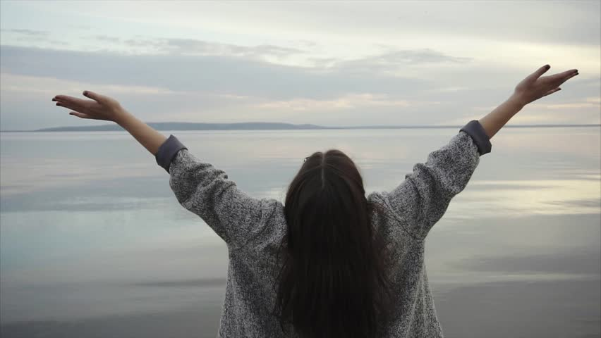 Young woman standing back to the camera and spreading her hands when looking at the sea. Make your life free. | Shutterstock HD Video #22248115