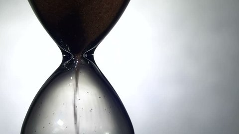 Hourglass on a White background, the sand falls inside. Close Up. Running Sand in the Sandglass. Egg timer emptying against a White background. Sands move through hour glass. Full HD 1920 x 1080p, 29