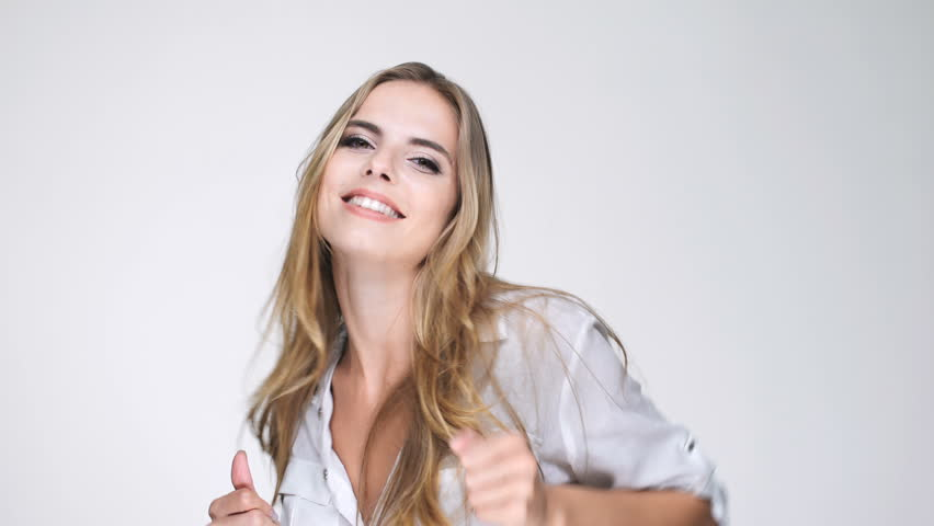 Cheerful pretty blonde woman in white shirt dancing and celebrating with hands up
