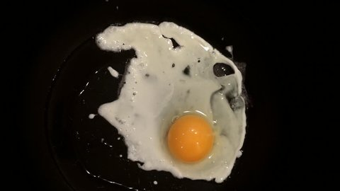 Sunny side up egg frying on a pan. Overhead shot