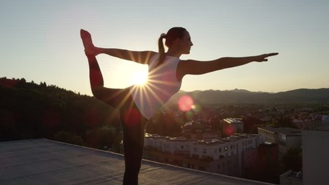 SLOW MOTION, CLOSE UP: Woman standing on the edge doing lord of the dance pose on top of skyscraper above stunning green overgrown mountains and vivid urban town illuminated by golden setting sun