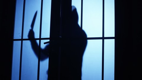 4K Silhouette of a killer or maniac with knife approaching to the door and entering to the room. Shot on RED Cinema Camera.