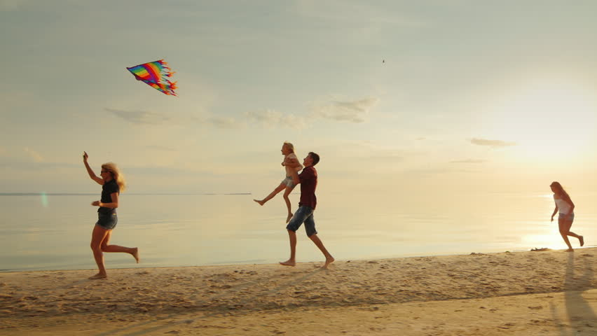 Mum plays with children kite. Children have fun and carefree running on the beach.