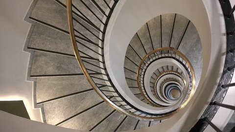 4K Beautiful spiral staircase in interior hall of house, stair circular rotation, handheld camera