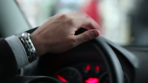 Closeup of person's hands on steering wheel driving car. Man driving a vehicle