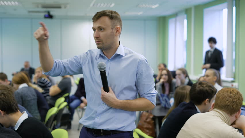 Professional coach in blue shirt speaking into the microphone and gesticulating at workshop for future top managers of a business company. Audience sitting at the conference room at the table