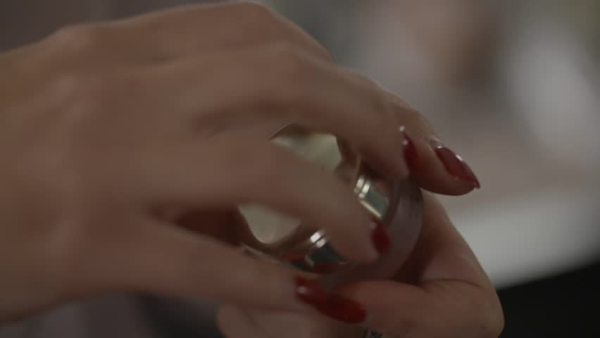 Opened glass jar of cream.Close-up picture of hands of a young woman holding in her hands and opening a bottle with facial cream
