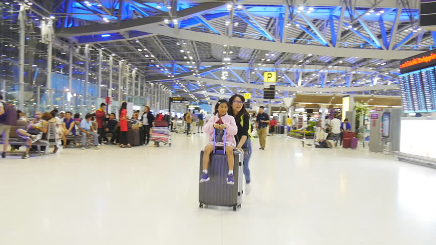 BANGKOK, THAILAND - OCTOBER 06, 2016 : Happy Asian girl sitting on luggage and running in the airport with her sister, while waiting for the plane