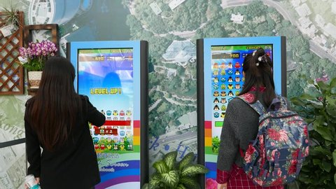 HONG KONG - FEBRUARY 10, 2015: Public entertainment corner inside HongKong park building. Two chinese girls plays video game on large vertical touch screens. Include original game sounds