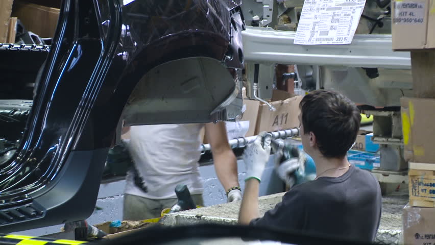 Man in the Process of Assembling Cars. Car Manufacturing. Working. Work in Process