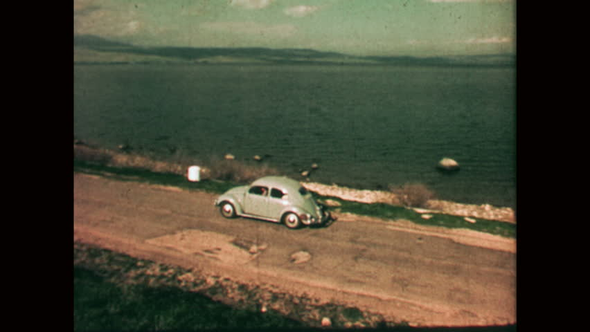 NAZARETH, ISRAEL: 1960s: VW Beetle drives along track next to coast. Motorboat on water. Sea of Galilee