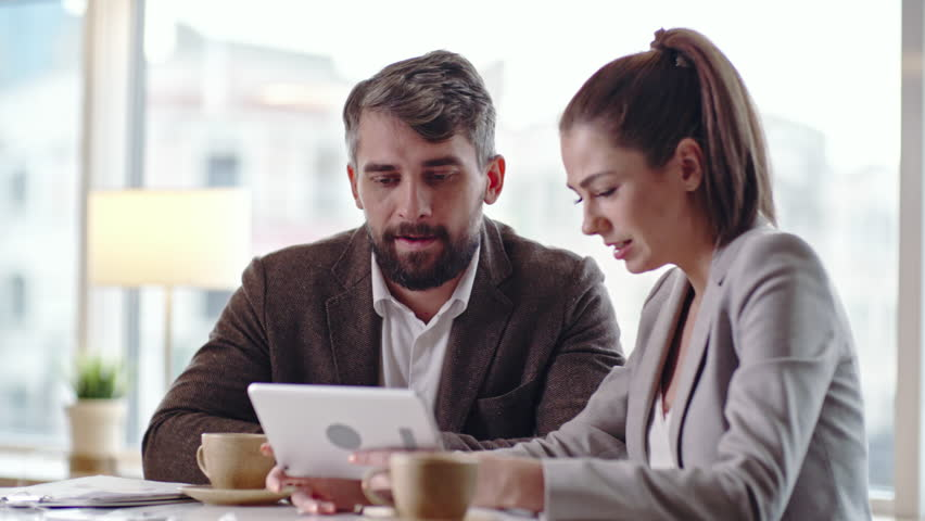 Businessman and businesswoman using digital tablet and discussing something at coffee break in the cafe | Shutterstock HD Video #22445119