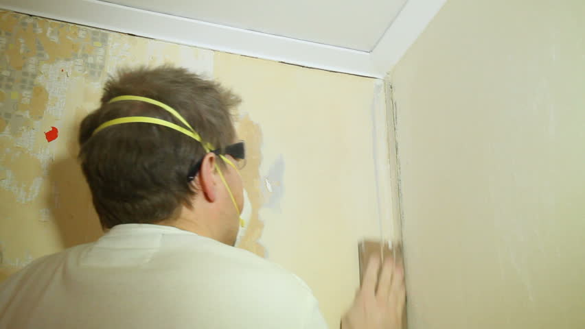 Man using sandpaper on old wallpaper.