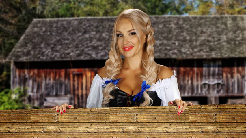 Young sexy Oktoberfest girl wearing a traditional Bavarian dress on the farm looks out from behind a wooden wall