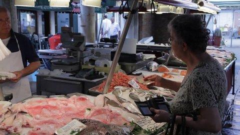 CIRCA 2011: MH Customer Buying Fish in Market / Venice, Italy