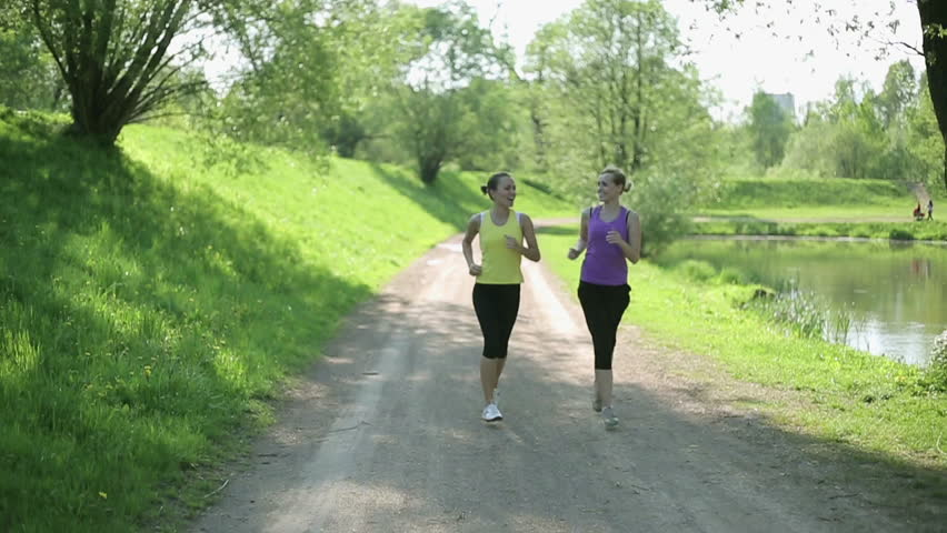 Two young girls jogging in the park, slow motion
