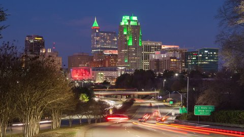 Raleigh NC Cityscape Night Timelapse with Moving Traffic Entering Downtown as the Sun Sets into the Night Showcasing the Lit Building Landscape of the North Carolina Capital City