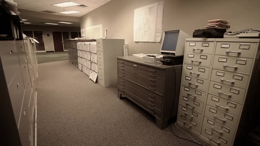 A Man Searches Through Large Filing Cabinets At His Business