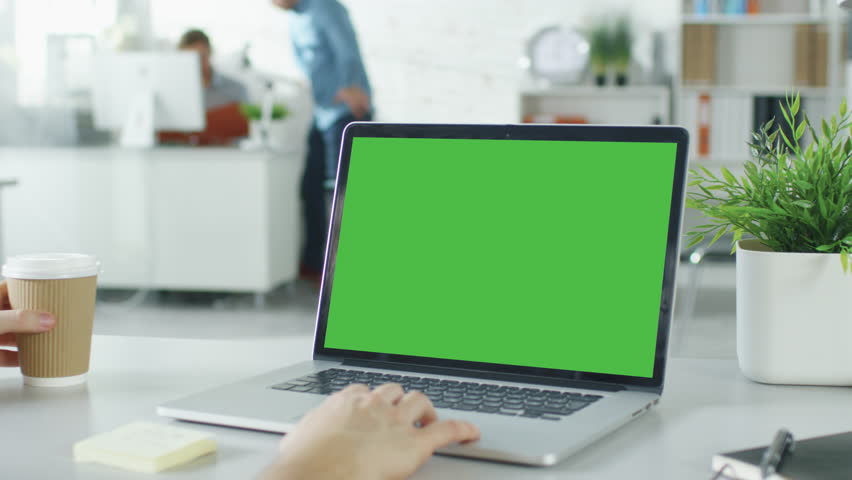 Close-up of a Man's Hands Working on Green Screen on a Laptop. In Background Blurred and Brightly Lit Office where One Man Approaches the Other and They Have Discussion. Shot on RED EPIC (uhd). #22521139