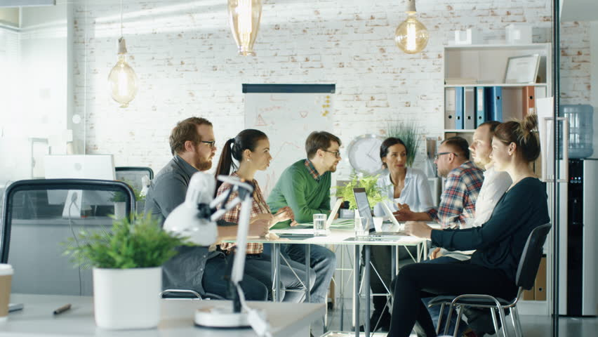 Seven Stylish People Having Planning Session Sitting at Big Table in their Creative Office. Shot on RED EPIC (uhd). | Shutterstock HD Video #22522180