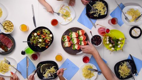 family diner by the table full of different tasty dishes, top view