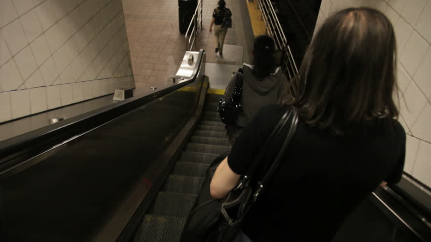 going down a subway escalator behind commuters who step onto the platform
