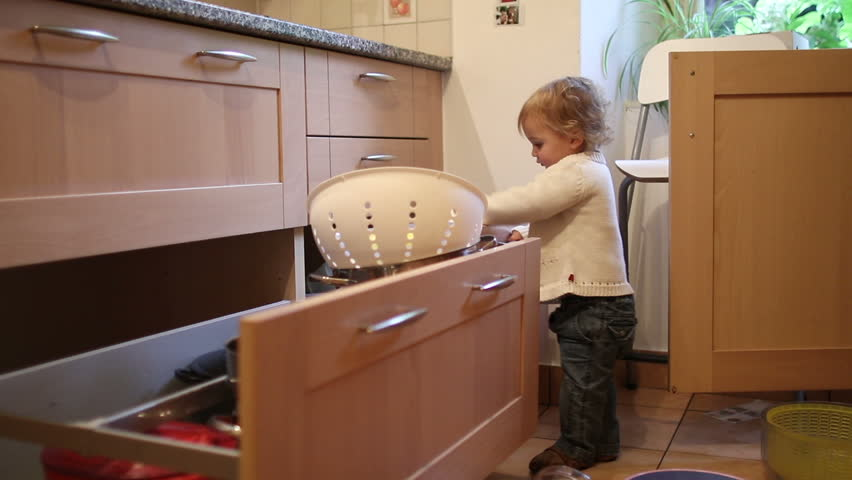 Baby Playing With Kitchen Utilities. Toddler At Play At The Kitchen With  Pots And Pans