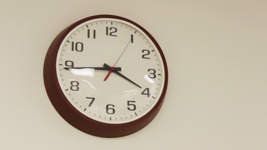 Boring office clock ticking on plain wall  December 25 2016