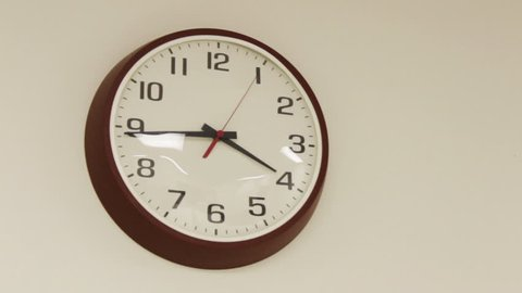 Boring office clock ticking on plain wall  December 25 2016
