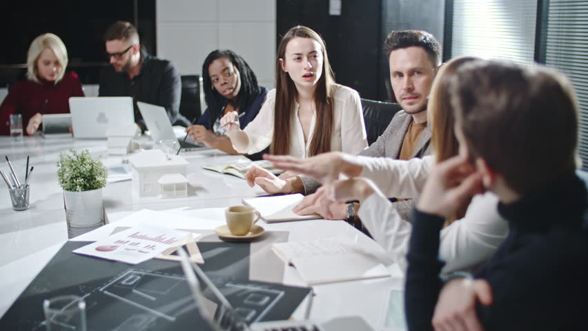 Multicultural young team working on architectural project together at business meeting   Shutterstock HD Video #22605619