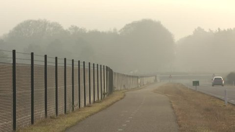 Fence alongside cycle path and road through Veluwe national park, to prevent wildlife vehicle collisions, car drives past and underpasses wildlife crossing. VELUWE, THE NETHERLANDS - DECEMBER 2016