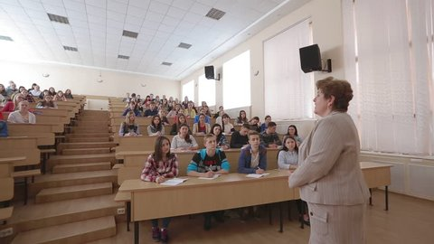 VINNITSA, UKRAINE - MAY 2016: Speaker giving presentation in lecture hall at university. Participants listening to lecture and making notes