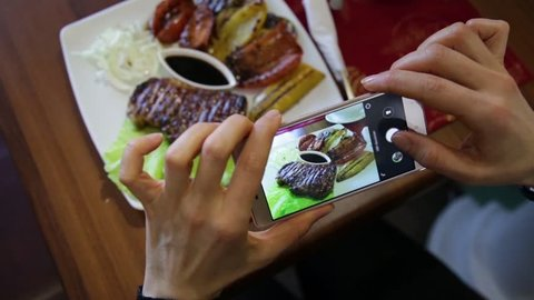 Trendy woman in a restaurant make photo of food with mobile phone camera for social network