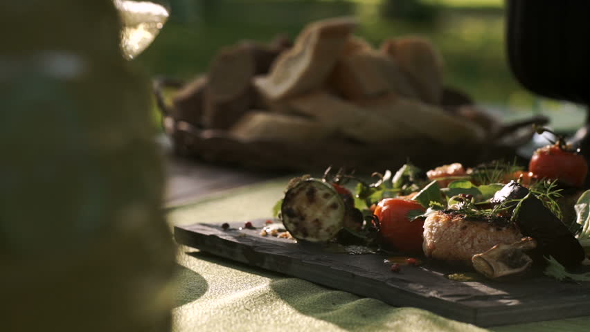 Catering. exquisitely decorated table with delicious meat, salads and wine for Romantic dinner in the forest. outdoor. sunny. picnic. slide.