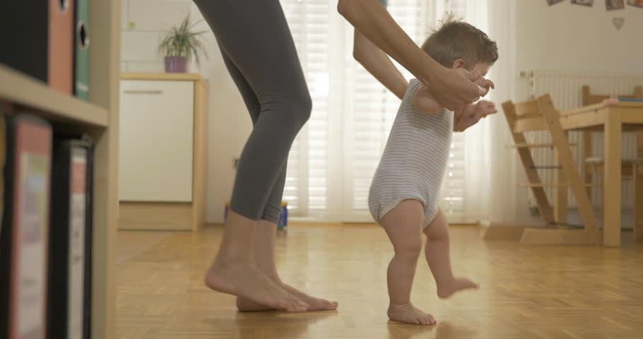 Side shot of an adorable baby boy walking barefoot across the kitchen with his mother holding him by his hands.