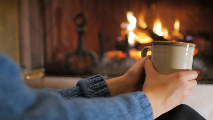 Hands with a cup of tea on a background of a burning fireplace. Comfort and warmth in the house