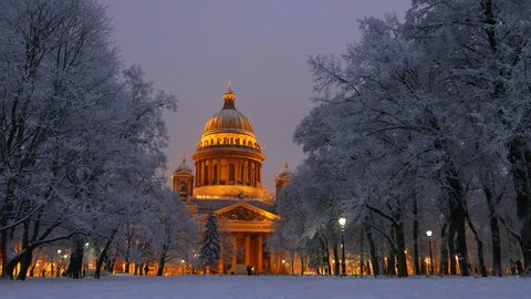 Saint Isaac's Cathedral seen between trees under snow, winter time, night shot. Famous and recognizable Saint Petersburg landmark - orthodox basilica, historical building named Isaakievskiy Sobor