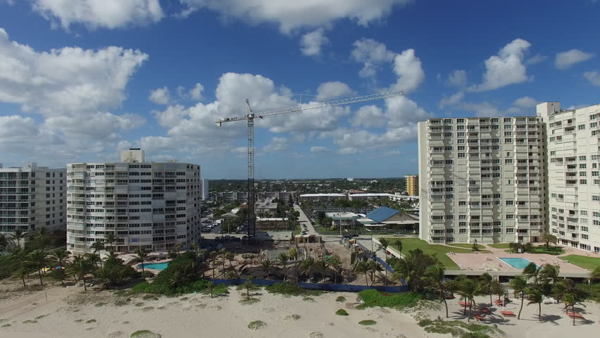Fly over Atlantic ocean to beach front construction in South Florida. Referencing building near ocean during sea level rise.