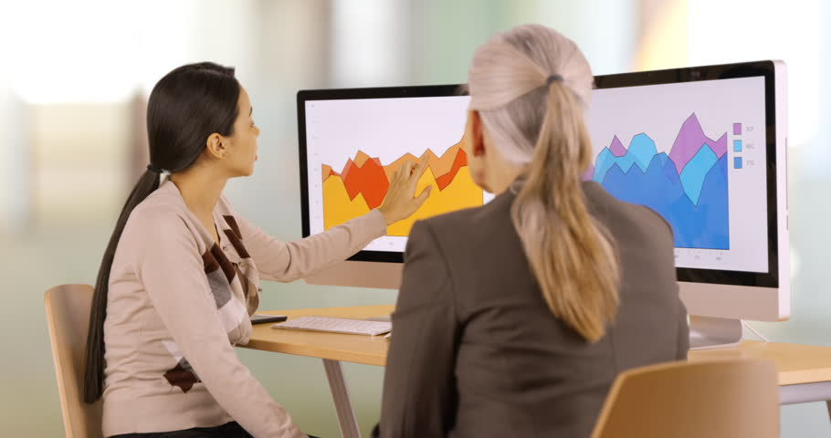 Two businesswomen discuss graphs. Business people have a conversation about the company. 4k | Shutterstock HD Video #22772353