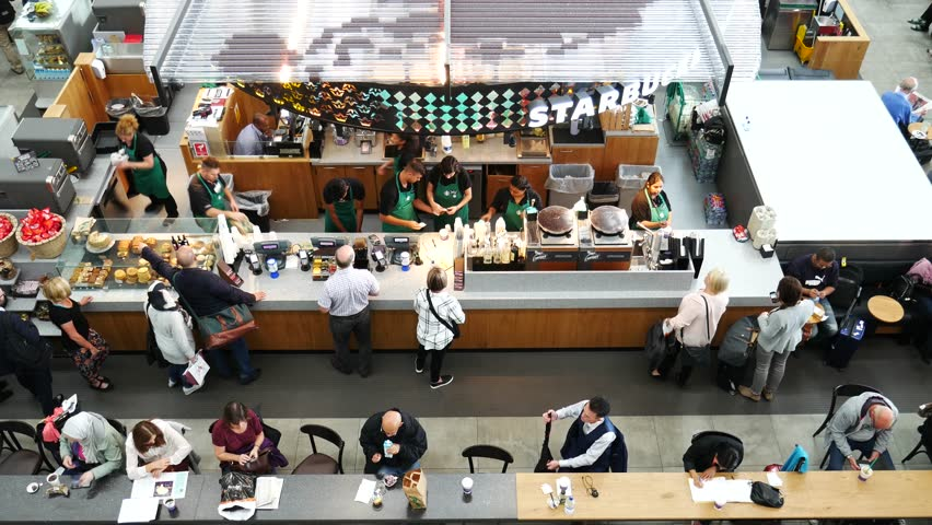 LONDON, UK - SEPTEMBER 29, 2016: People at Starbucks coffee shop at Heathrow airport on September the 29th, 2016 in London, England, UK. Heathrow is one of the busiest airports in the world
