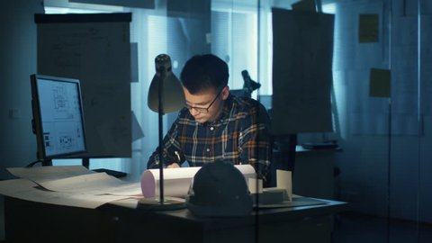 Young Capable Architectural Engineer Working Late Hours in His Office. Office is Dark Only His Table Light is On. Various Plans and Blueprints Lying on the Table. He Draws in His Notepad.